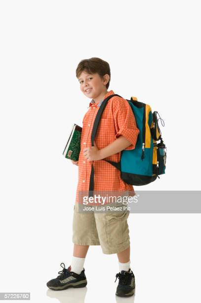 Young student carrying books and backpack while smiling for the camera