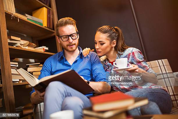 young student couple learning together from a book. - emir memedovski stock pictures, royalty-free photos & images