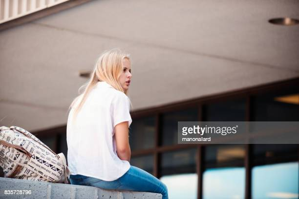 Young student girl back to school sitting in front of school