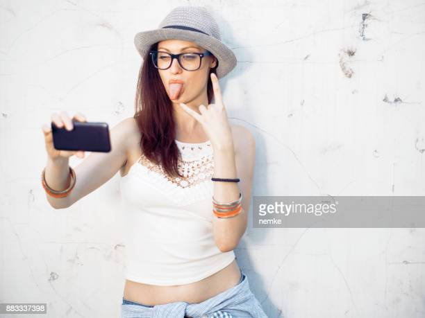 young student girl sticking out tongue and taking selfie - naughty america member stock photos and pictures