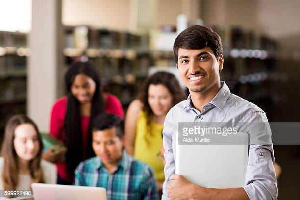 young student holding a laptop computer and smiling - nepalese ethnicity stock pictures, royalty-free photos & images