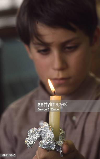 A young student intently watches the flame of a candle that he holds in a piece of crumpled foil Peekskill New York late 1960s