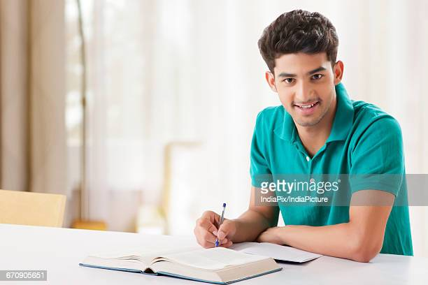 Young student is sitting on desk with open book and learns for his exams