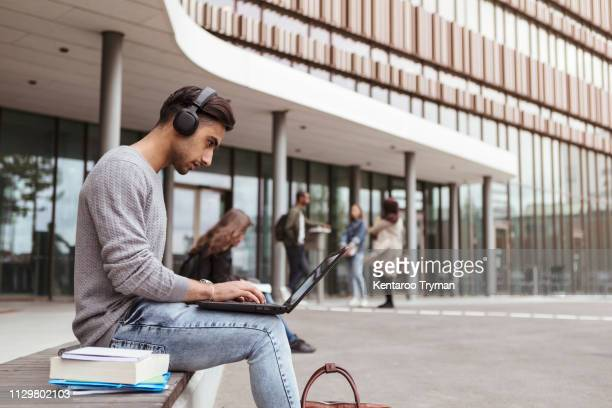 young student listening music while using laptop at university campus - post secondary education stock pictures, royalty-free photos & images