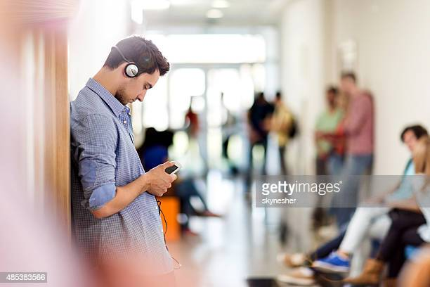 young student listening to mp3 player in school lobby. - music halls stock pictures, royalty-free photos & images