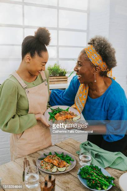 young student looks bashful as she presents a plated salmon meal to her teacher - crucifers stock pictures, royalty-free photos & images