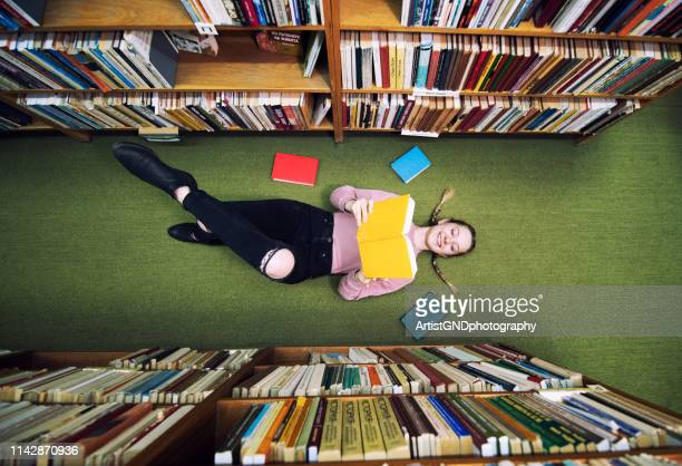 young student lying on the floor in library and reading book. - book shop stock pictures, royalty-free photos & images
