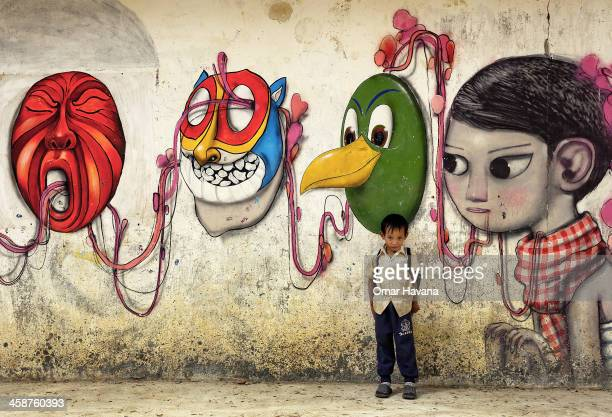 A young student of Phare Ponleu Selpak school poses in front of a wall mural painted by visual artist of the circus on December 20 2013 in Battambang...