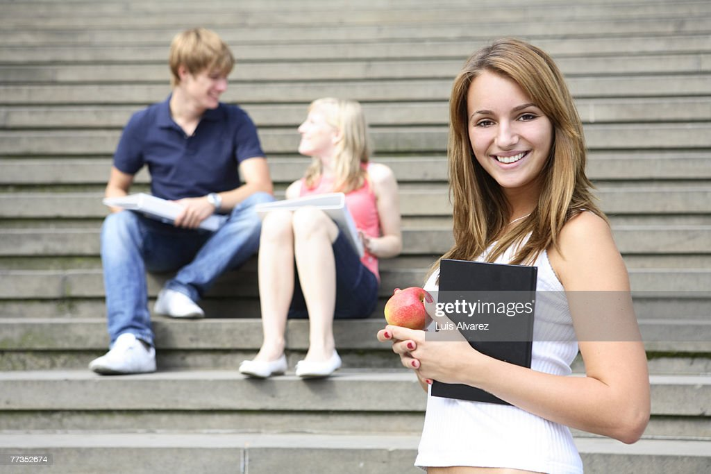 Young student on campus with book and apple. Other students in background : Stock Photo