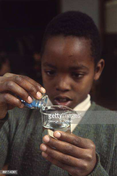 Young student pours drops of a blue liquid into a beaker of clear liquid, Peekskill, New York, late 1960s.