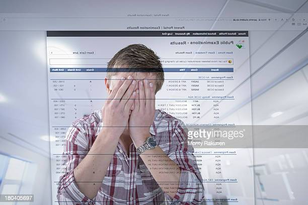 Young student reacting to examination results displayed on screen