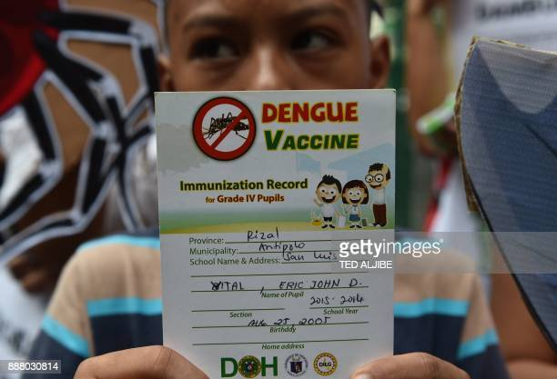 A young student shows his vaccine record as he joins others in a protest in front of the Department of Health office in Manila on December 8 against...