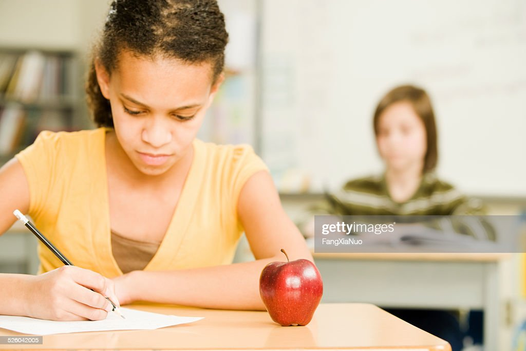 Young Student Sits At Her Desk With An Apple : Stock Photo