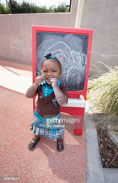 Young student smiling outdoors at preschool