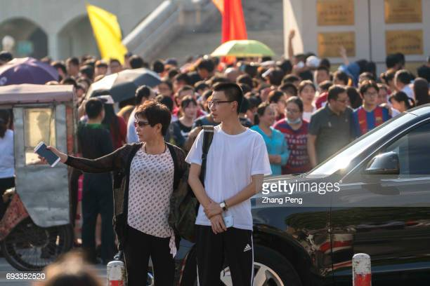 A young student together with his mother walk past the crossroad after finishing the first subject of the college entrance exam From June 7th to 9th...