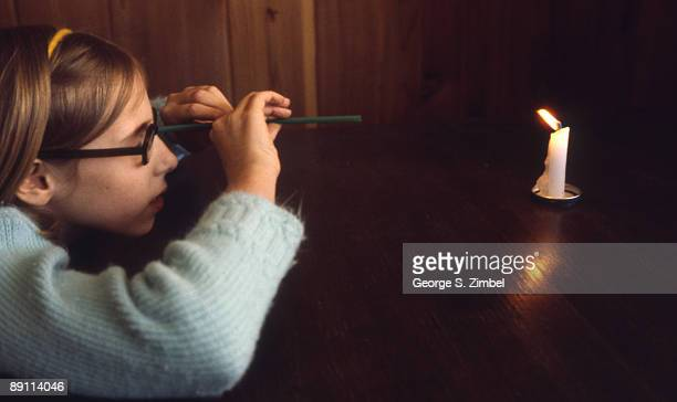 Young student watches the flame of a candle through a small straw, Peekskill, New York, late 1960s.