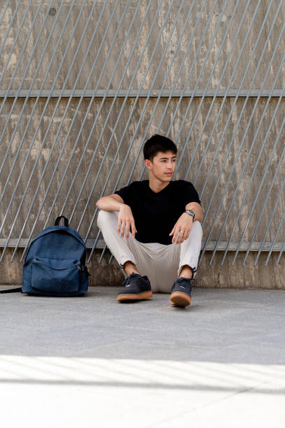Young student with backpack sitting on floor, looking away