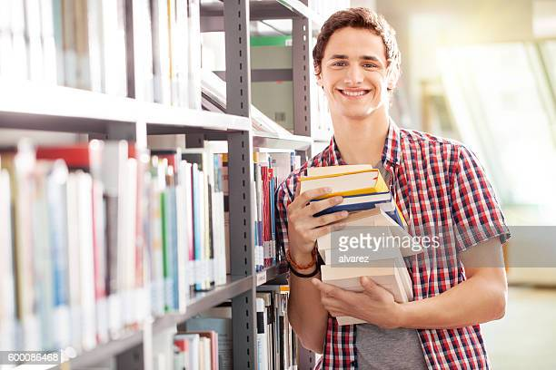 Young student with books in library