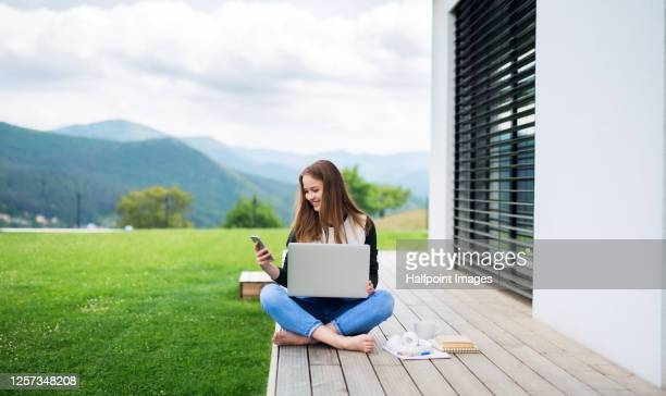 young student with laptop learning outdoors at home, homeschooling concept. - patio de colegio - fotografias e filmes do acervo