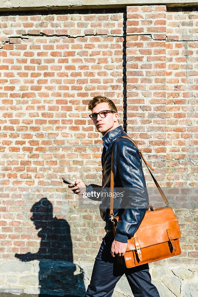 Young student with shoulder bag and smartphone : Stock Photo