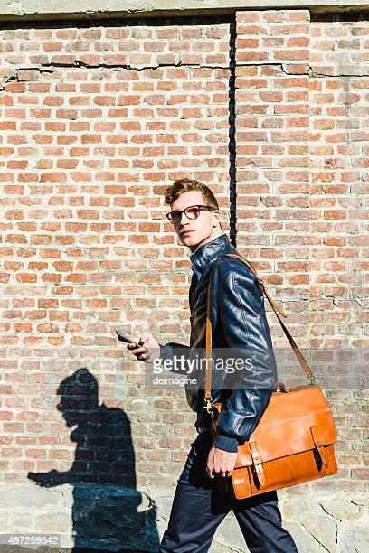 giovane studente con borsa a tracolla e uno smartphone - 20 24 anni foto e immagini stock