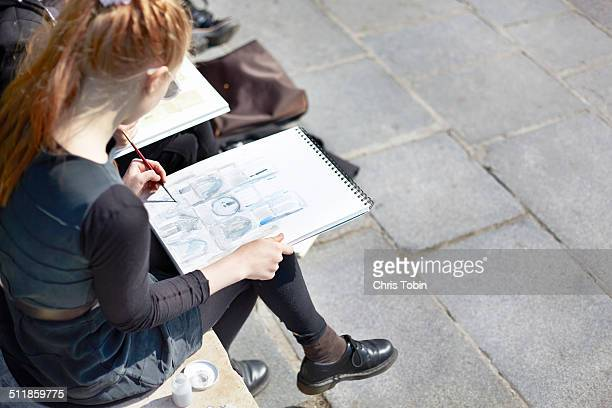 Young student with sketchbook Notre Dame Paris