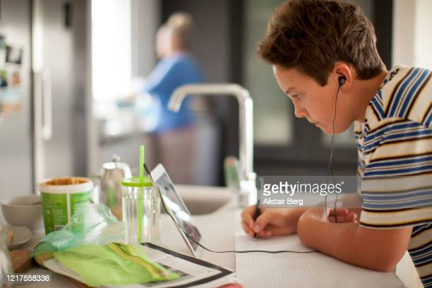 young student working on digital tablet in his kitchen during lockdown - abstand halten infektionsvermeidung stock-fotos und bilder