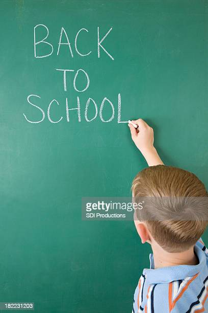 Young Student Writing Back to School on Chalk Board