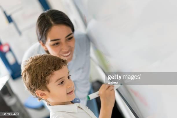 Jonge student met de docent naast hem op het bord schrijven