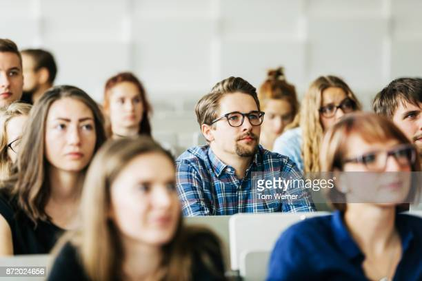 young students concentrating on professor during lecture - vortrag stock-fotos und bilder