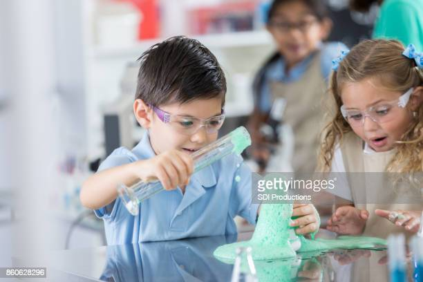 Young students conduct chemistry experiment