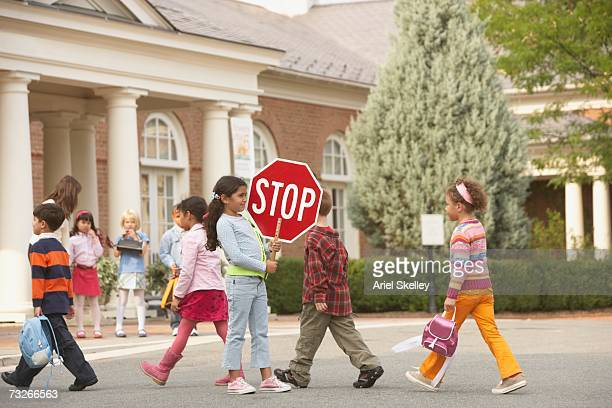 Young students crossing street with student crossing guard