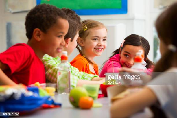 jeunes étudiants appréciant leur déjeuner à l'école - cantine photos et images de collection