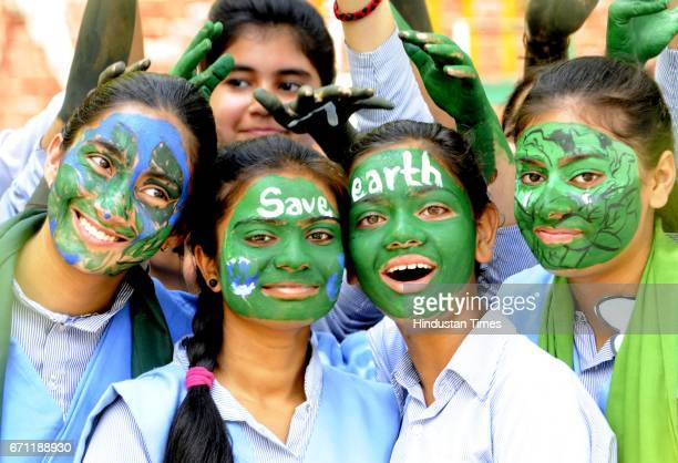 Young students pose with their painted faces to create awareness on World Earth Day at Blossoms Sr Sec School on April 21 2017 in Patiala India Earth...