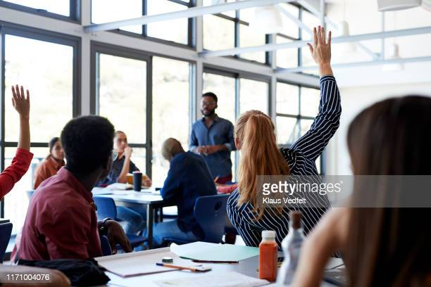 young students raising hands in classroom - q and a stock pictures, royalty-free photos & images