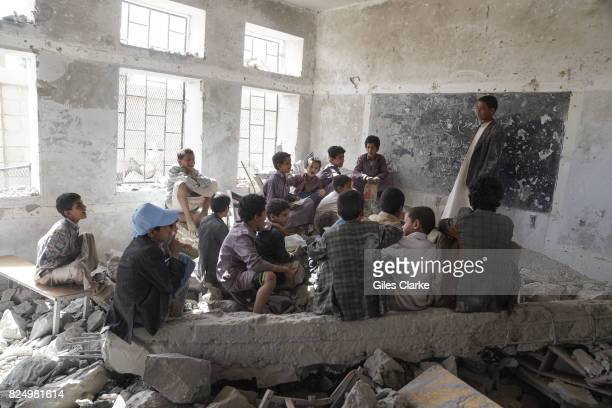 Young students sit in a former damaged classroom at their local school Students now attend lessons in UNICEF tents nearby