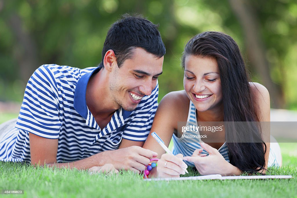 Young students sitting on green grass with note book. : Stock Photo