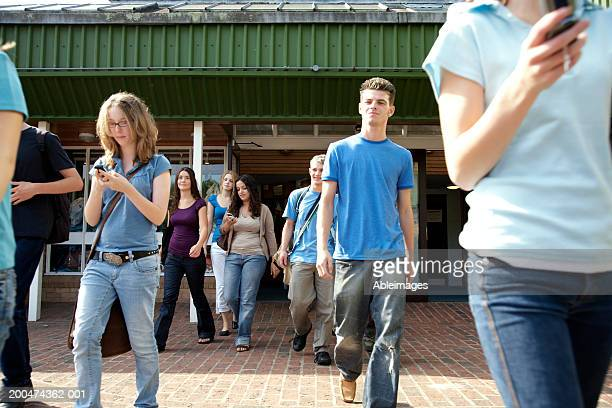 Young students walking out of college