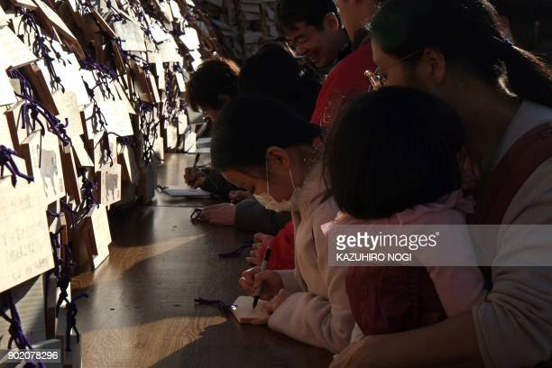 Young students write their wishes on Ema wooden votive tablets with wishes on them at Yushima Tenmangu Shrine in Tokyo on January 7 2018 Many...