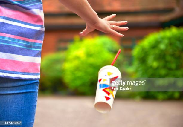 young student/teenager dropping litter - rubbish stock pictures, royalty-free photos & images