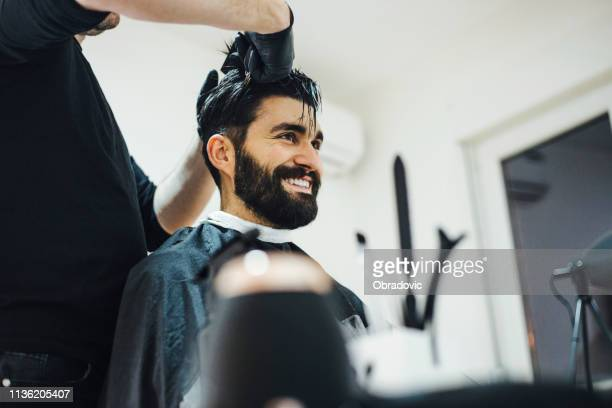 young stylish barber with mustache and tattoos giving man haircut - hairstyle stock pictures, royalty-free photos & images