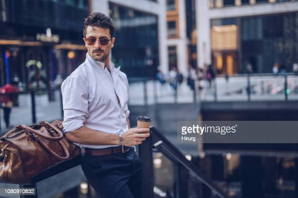 young stylish businessman having takeaway coffee - elegância imagens e fotografias de stock