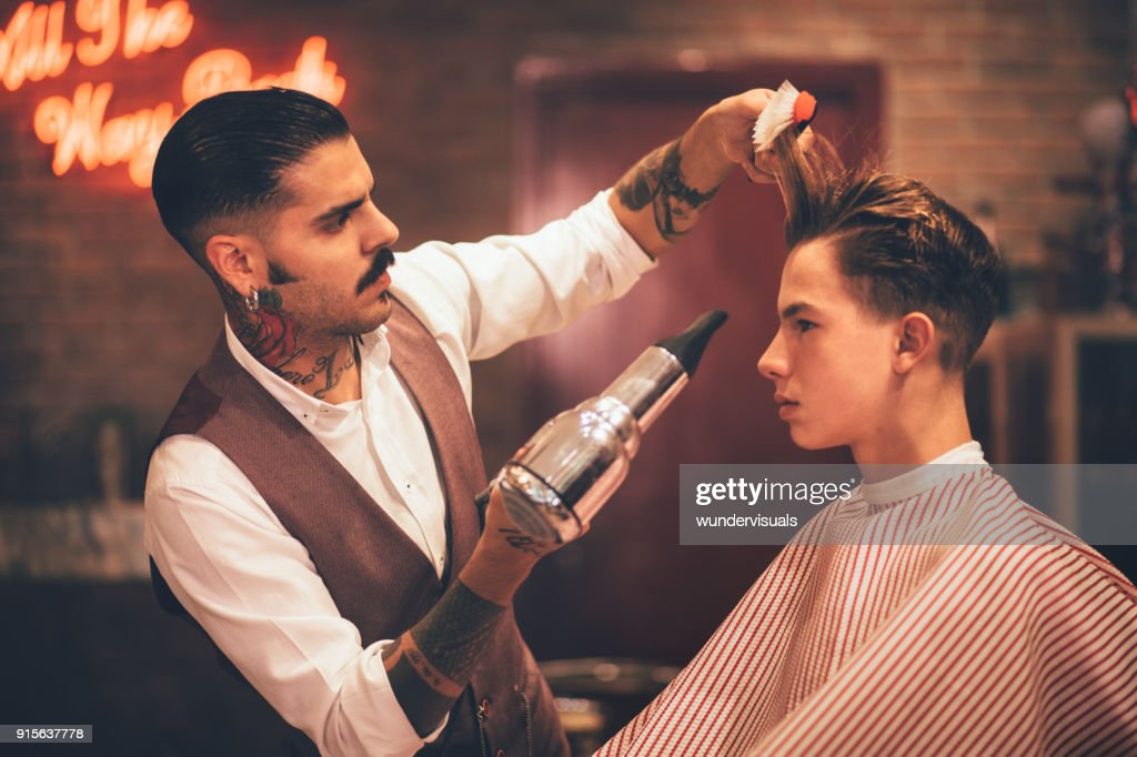 Young stylish hairdresser blow drying hipster man's hair : Stock Photo