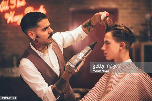 Young stylish hairdresser blow drying hipster man's hair