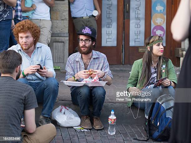 Young, stylish hipsters sit on the curb while eating street food on 6th Street in Austin, Texas during SXSW 2013