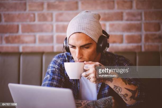 Ung snygg man dricka kaffe och lyssna på musik