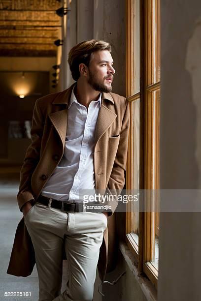 Young stylish man looking thrue window
