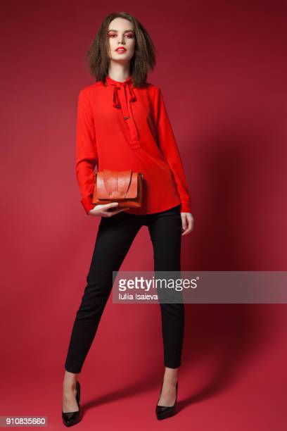 young stylish woman in studio - sac à main rouge photos et images de collection