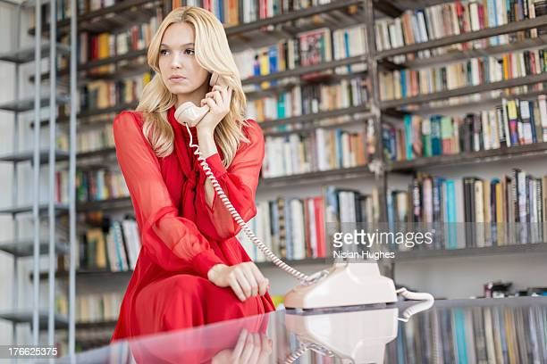 young stylish woman on a call using rotary phone