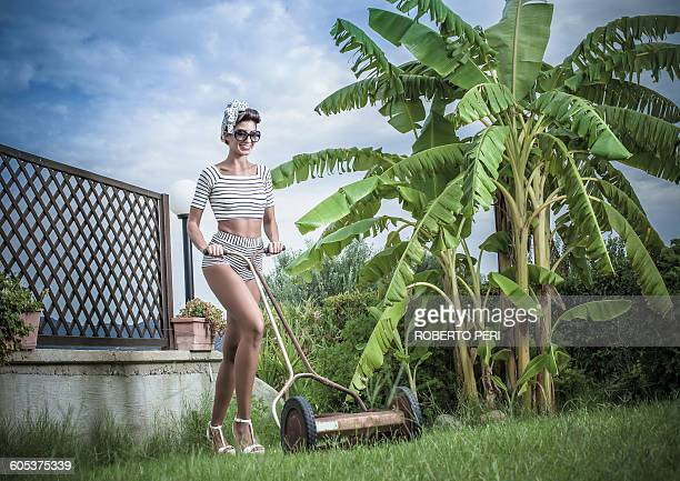 Young stylish woman pushing lawnmower in garden
